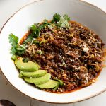 Bowl of chili garnished with avocado, cheese, and cilantro