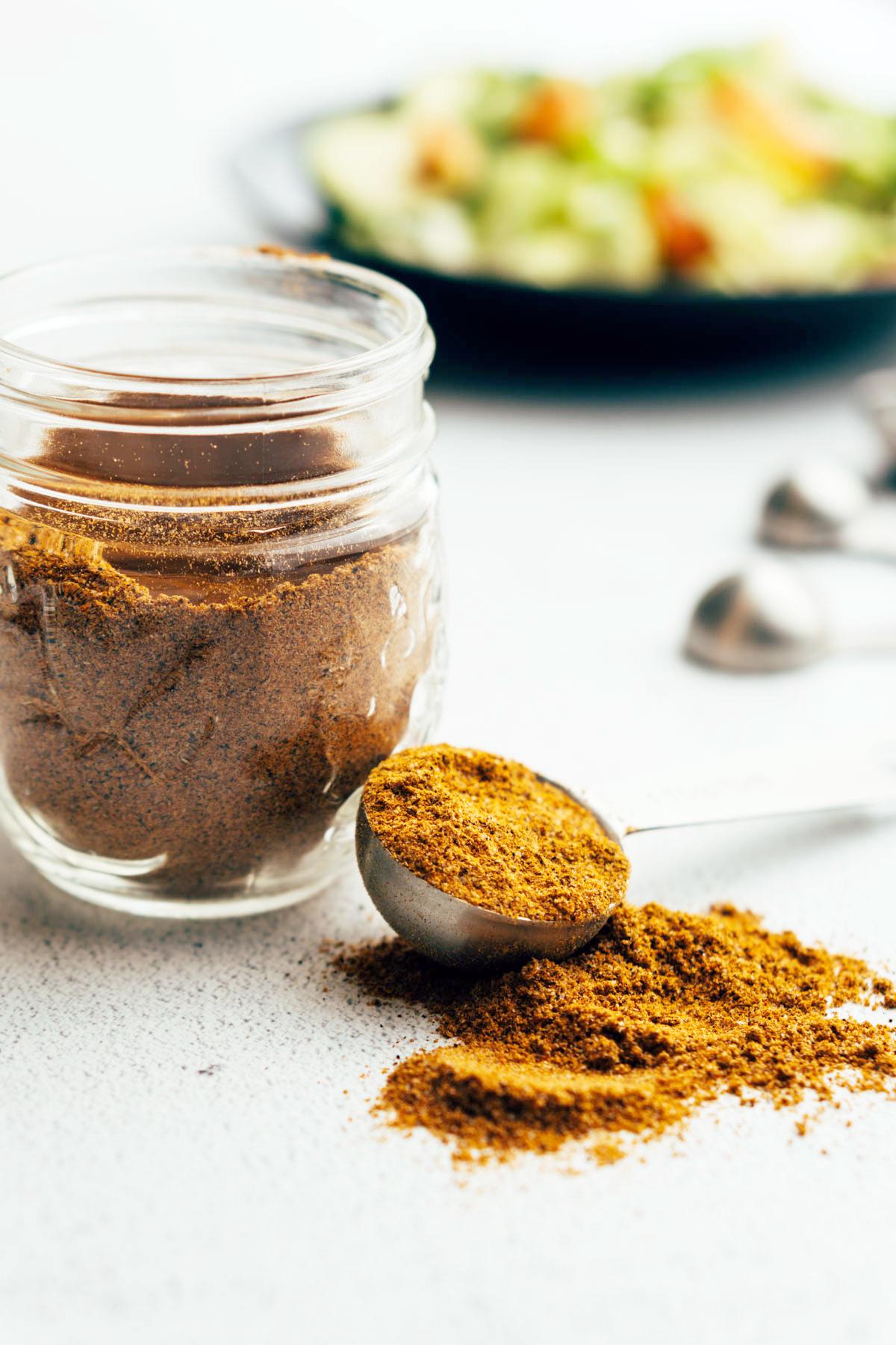 Spilled seasoning near mason jar and salad.