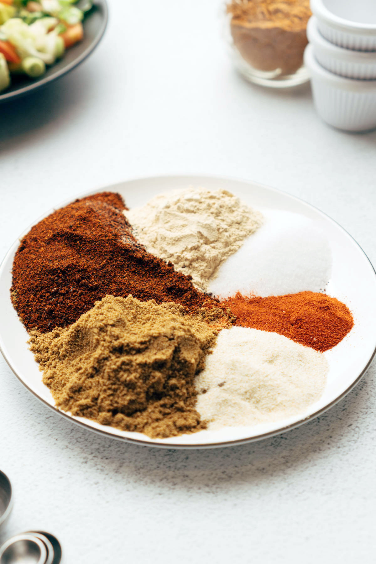 Spices for taco seasoning on plate.
