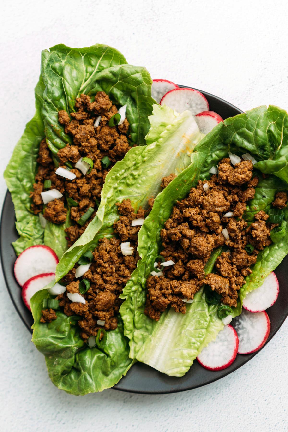 Keto taco meat in lettuce leaf wrap on plate.