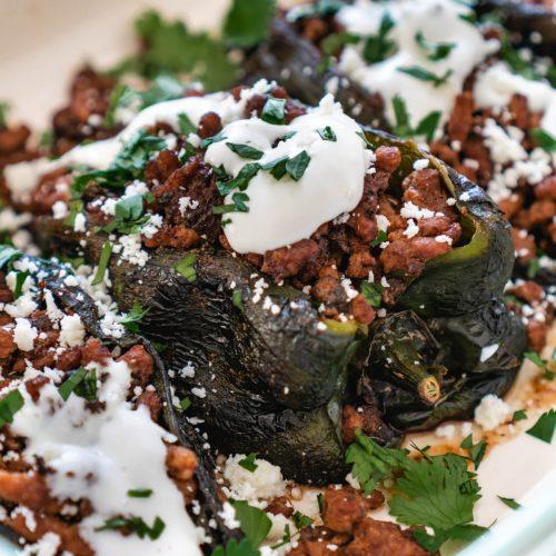 Up close photo of roasted poblano pepper with chorizo sausage and crema cotija garnish
