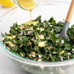 Pouring salad dressing over kale salad in bowl.